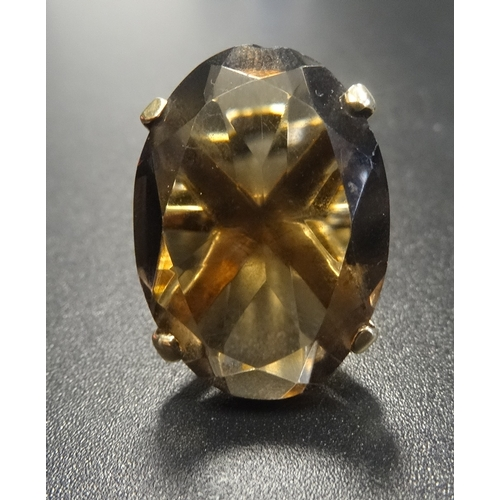 131 - SMOKY TOPAZ SINGLE STONE DRESS RING  the oval cut topaz on nine carat gold shank with raised setting...