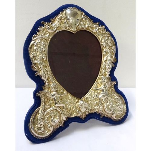 156 - VICTORIAN STYLE SILVER PHOTOGRAPH FRAME the heart shaped frame with profuse scroll, floral and cheru...
