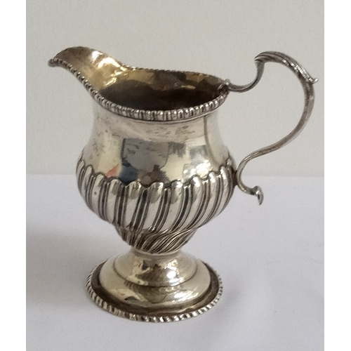 162 - GEORGE III SILVER CREAM JUG with gadrooned decoration to the body and a beaded rim, London hallmarks...