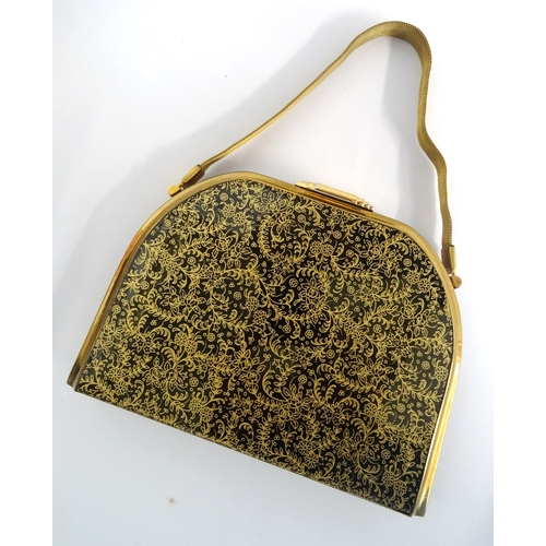 320 - 1950s HARD SHELL EVENING BAG BY STRATTON with floral gilt decoration on a black ground, opening to r...