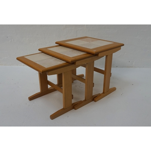 406 - NEST OF THREE OAK TILE-TOP TABLES  raised on shaped ends with stretchers, the largest 44.8cm wide...