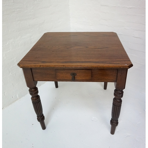 411 - EDWARDIAN OAK TEA TABLE  the square top with canted corners, single drawer and raised on long turned...