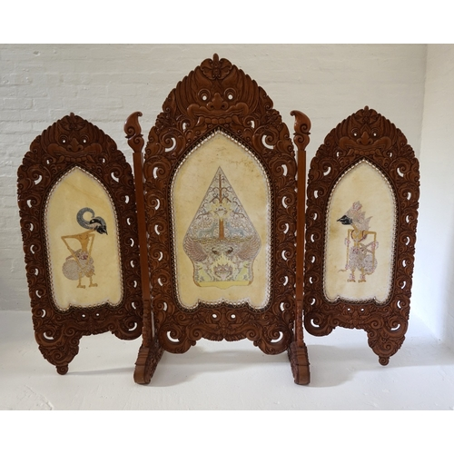 419 - LARGE INDONESIAN HEAVILY CARVED TEAK 'SKETSEL WAYANG'  in three sections, the frame decorated with m...