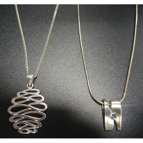 43 - TWO SILVER PENDANTS one set with blue topaz and the other of graduated entwined loop design, both on...