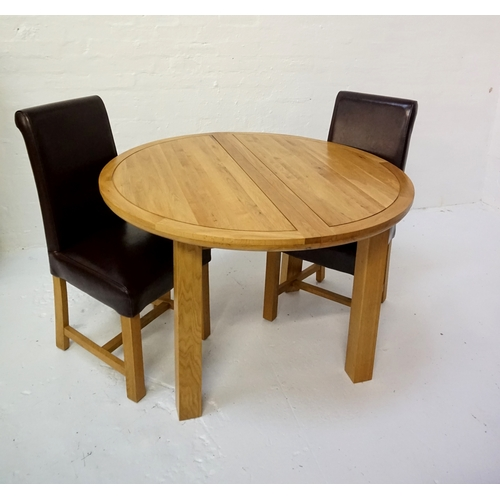 423 - CIRCULAR LIGHT OAK EXTENDING DINING TABLE with a pull apart top revealing a fold out leaf, standing ...
