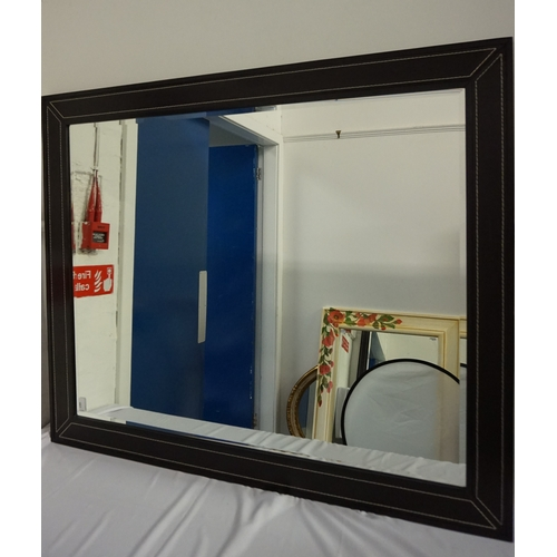 415 - LARGE STAINED OAK FRAME MIRROR with inset leather panels with decorative stitching, encasing a bevel...