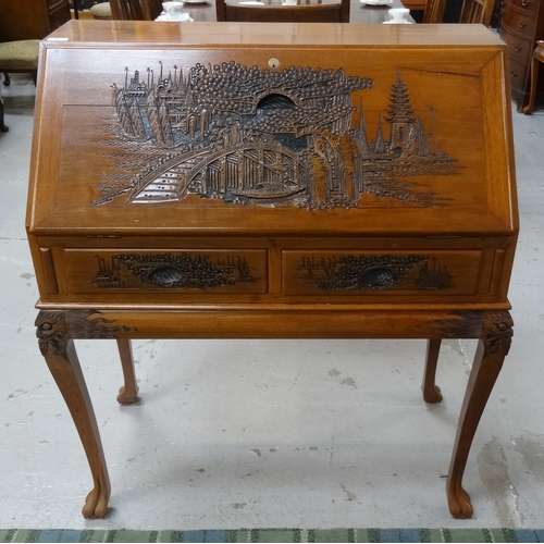 390 - MALAYSIAN TEAK BUREAU on a stand, with a carved fall flap and sides above two carved frieze drawers ...