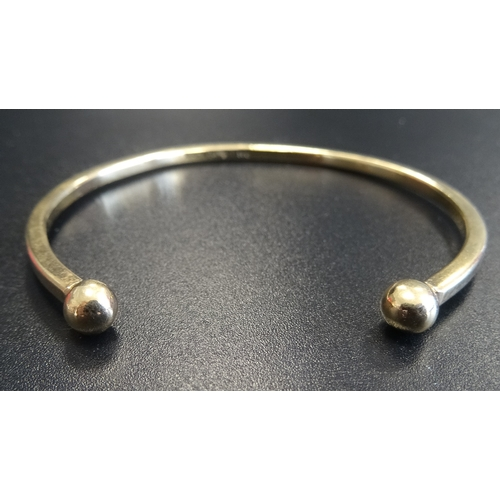 1 - NINE CARAT GOLD BANGLE with ball finials, approximately 11.7 grams...
