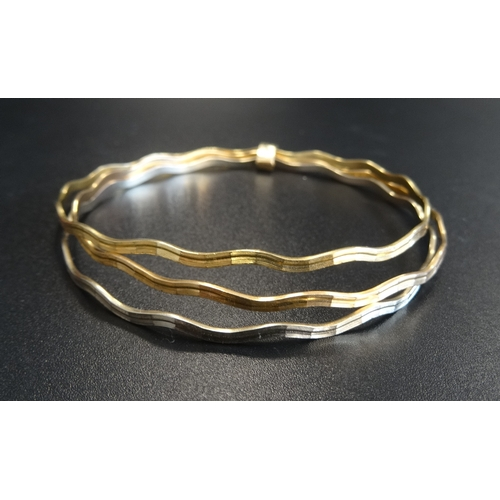 11 - EIGHTEEN CARAT GOLD RUSSIAN WEDDING RING STYLE TRIPLE BANGLE comprising wavy white, yellow and rose ...