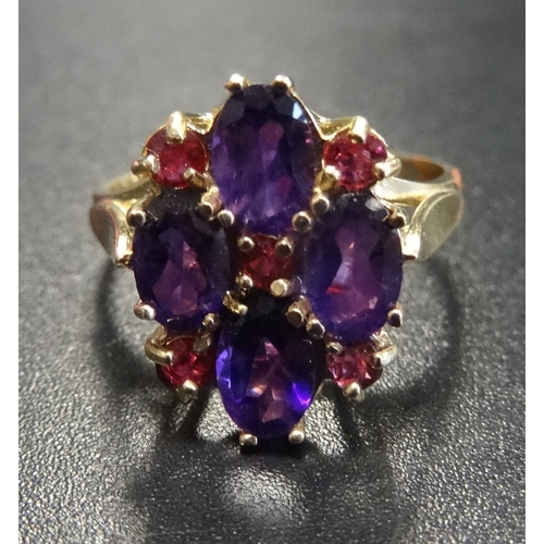 21 - UNUSUAL AMETHYST AND RUBY CLUSTER RING the four oval cut amethysts interspersed with small rubies, o...