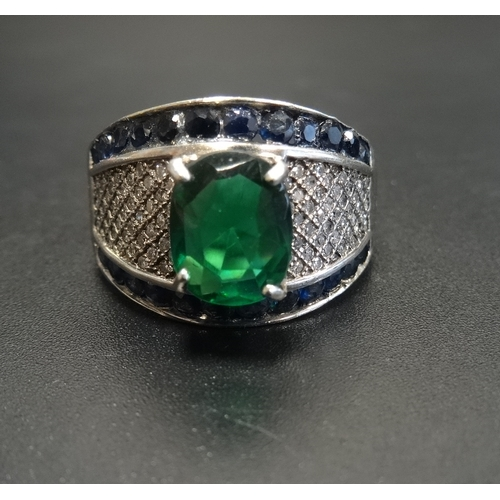 33 - UNUSUAL DIAMOND, SAPPHIRE AND GREEN STONE SET DRESS RING the central oval cut green stone flanked by...