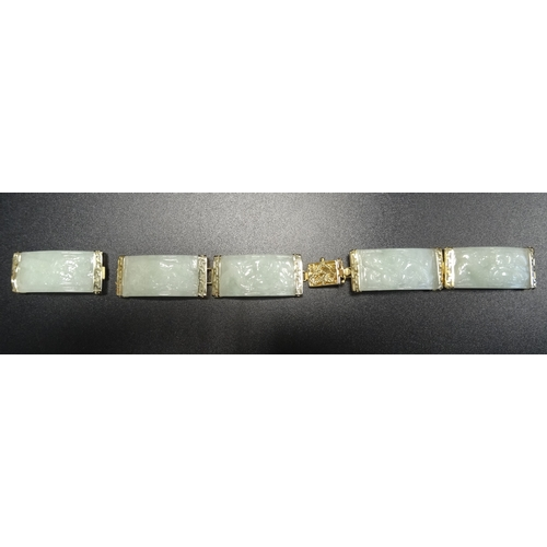 44 - CARVED JADE AND FOURTEEN CARAT GOLD BRACELET the five jade panels carved with dragon decoration, in ...