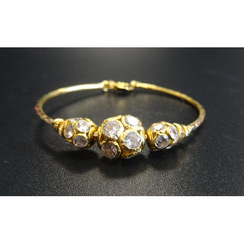 59 - TWENTY-TWO CARAT GOLD CHILD'S BRACELET with crystal decoration, 4.4cm diameter, total weight approxi...