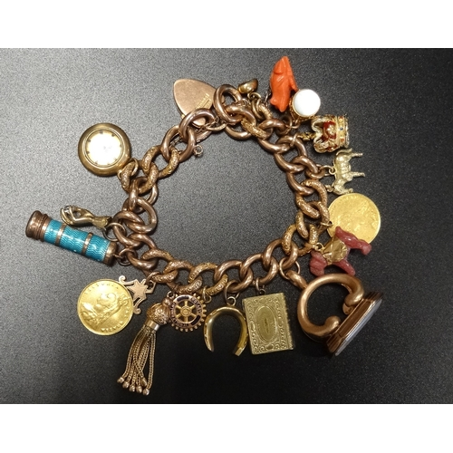 61 - NINE CARAT GOLD CURB LINK CHARM BRACELET with a good selection of gold and other charms, including a...