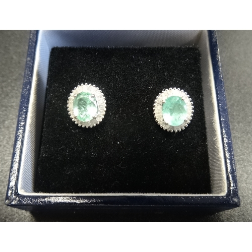 64 - ATTRACTIVE PAIR OF GREEN GEM AND DIAMOND CLUSTER EARRINGS the central oval cut stones possibly green...