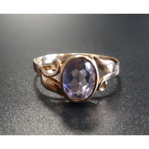 7 - AMETHYST SINGLE STONE RING the oval cut amethyst flanked by pierced scroll decorated shoulders, on n...
