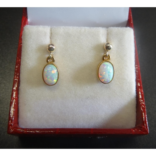 12 - PAIR OF OPAL DROP EARRINGS the oval cabochon opals in nine carat gold...