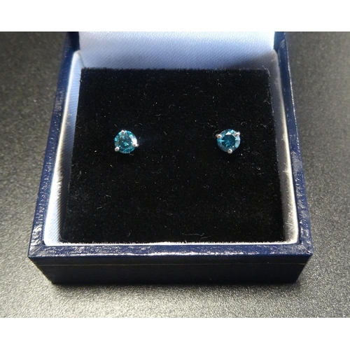 15 - PAIR OF BLUE DIAMOND STUD EARRINGS in eighteen carat white gold, the diamonds totalling approximatel...