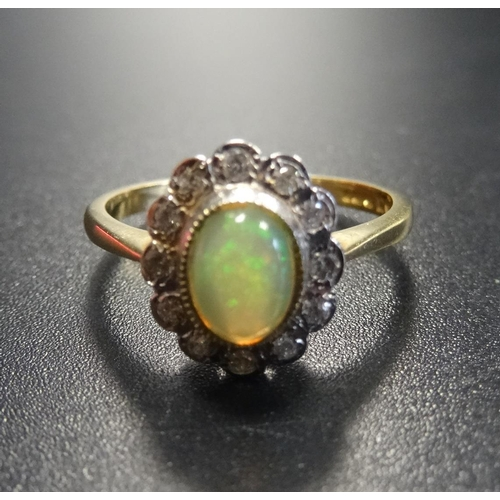 19 - OPAL AND DIAMOND CLUSTER RING the central opal in twelve diamond surround, on eighteen carat gold sh...