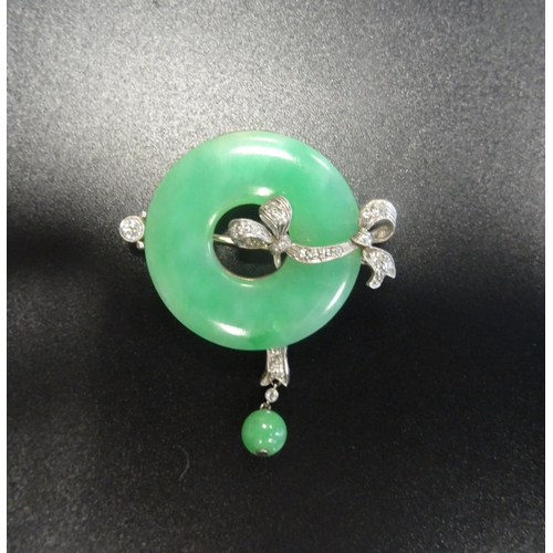 24 - ATTRACTIVE JADE AND DIAMOND BROOCH the ring of green jade with diamond set ribbon detail and further...
