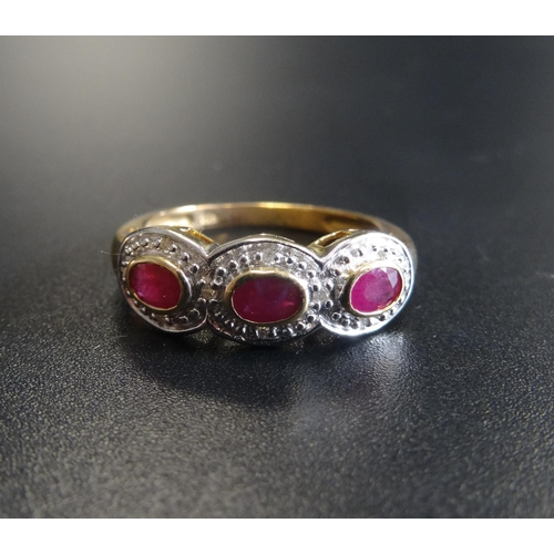 41 - RUBY AND DIAMOND DRESS RING the three oval cut rubies in textured surround set with small diamonds, ...