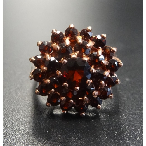44 - GARNET CLUSTER DRESS RING the central garnet in double garnet surround, on nine carat rose gold shan...