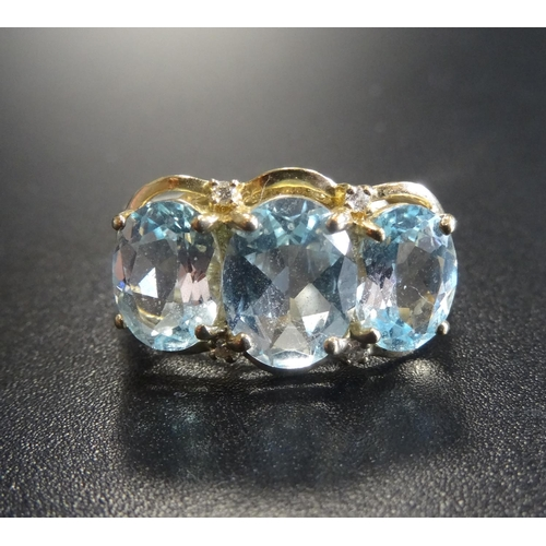 48 - AQUAMARINE AND DIAMOND DRESS RING the three oval cut aquamarines with two small diamonds above and b...