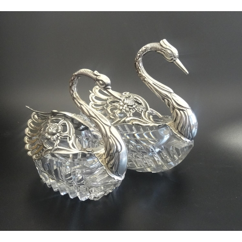 181 - TWO GRADUATED SILVER MOUNTED CUT GLASS TABLE SALTS in the form of swans with articulated pierced sil...