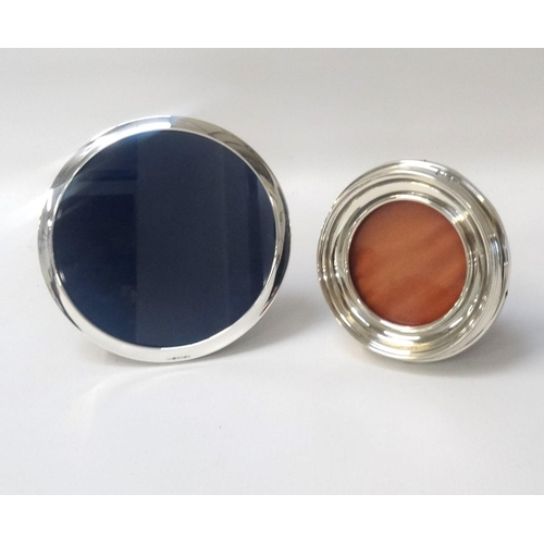183 - TWO CIRCULAR SILVER PHOTOGRAPH FRAMES of graduated size, both on easel supports, the smaller example...