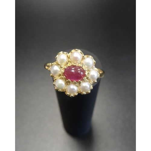 7 - RUBY AND PEARL CLUSTER DRESS RING the central oval cabochon ruby in eight diamond surround, on eight...