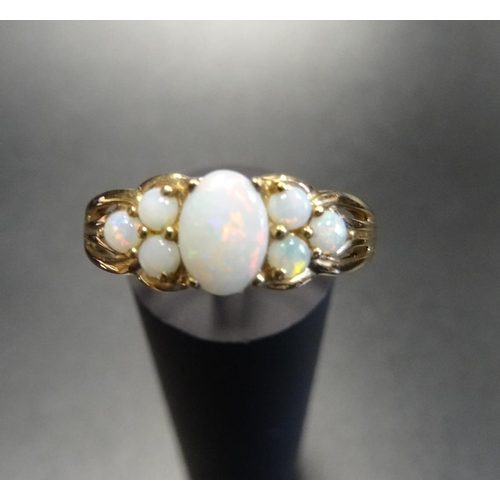 18 - OPAL CLUSTER RING the central oval cabochon opal flanked by three round cabochon opals to each side,...