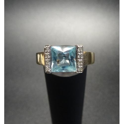 27 - AQUAMARINE AND DIAMOND DRESS RING the princess cut aquamarine flanked by a vertical row of diamonds ...