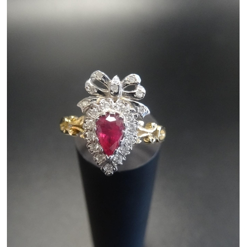 32 - UNUSUAL RUBY AND DIAMOND CLUSTER RING the pear cut ruby in diamond surround and surmounted by a diam...