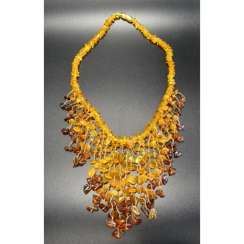 42 - MODERN AMBER BEAD NECKLACE the varying shades of amber in graduated fringed front piece, approximate...
