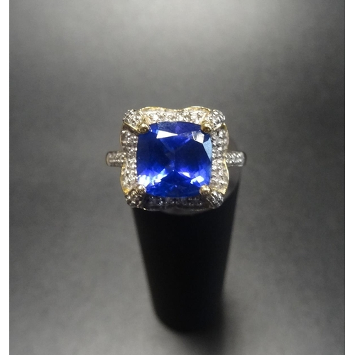 48 - IMPRESSIVE TANZANITE AND DIAMOND CLUSTER DRESS RING the central cushion cut tanzanite approximately ...