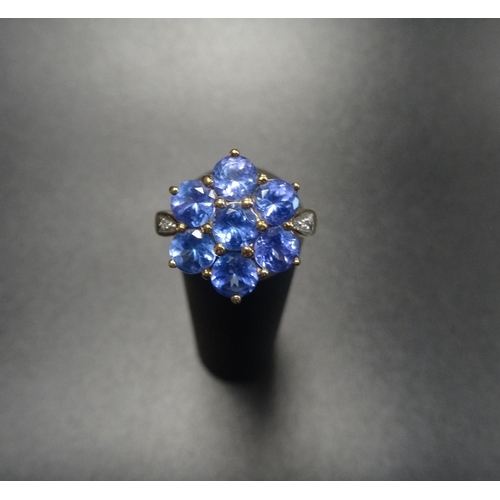 51 - TANZANITE CLUSTER DRESS RING the seven stone tanzanite cluster flanked by a small diamond to each sh...