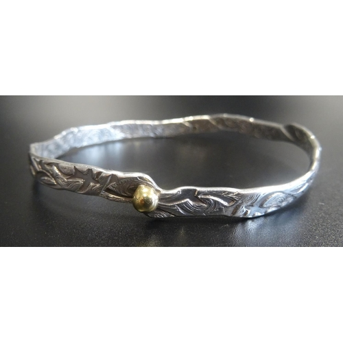 4 - MALCOLM APPLEBY SILVER BANGLE of irregular form with stylised motif decoration overall and gold bead...