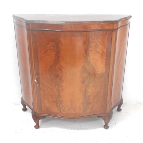 523 - MAHOGANY CREDENZA of shaped outline with a central door opening to reveal a shelved interior, standi...