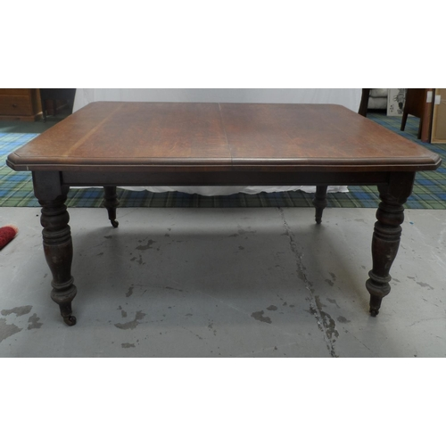 524 - LATE VICTORIAN OAK DINING TABLE with canted corners to the wind out top, standing on turned and tape...