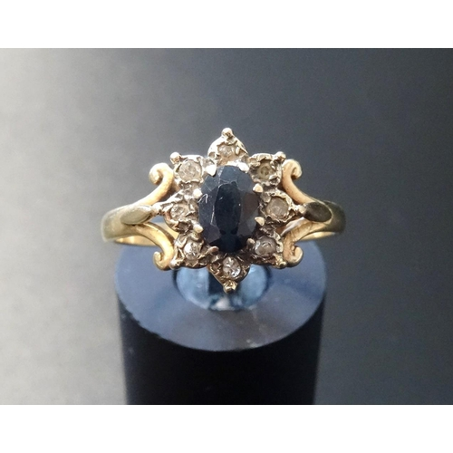 21 - SAPPHIRE AND DIAMOND CLUSTER RING the central oval cut sapphire in diamond surround, on nine carat g...