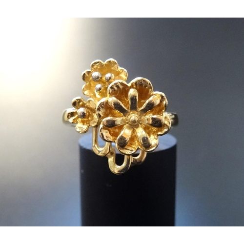 31 - EIGHTEEN CARAT GOLD FLOWER DESIGN RING the larger flower head beside two smaller examples, ring size...