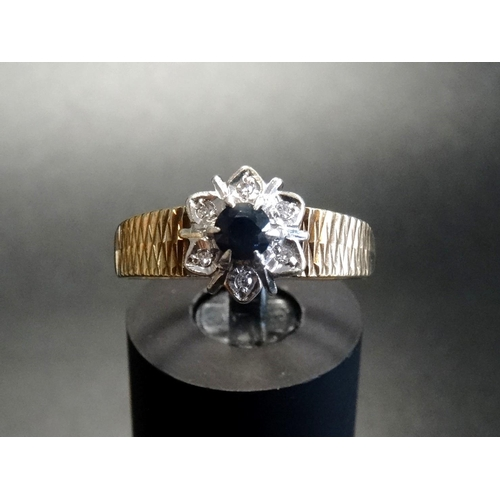22 - SAPPHIRE AND DIAMOND CLUSTER RING the central round cut sapphire approximately 0.2cts in illusion se...