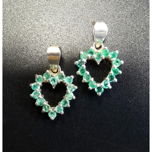 30 - TWO EMERALD SET HEART SHAPED PENDANTS each pendant set with fourteen emeralds, in silver...