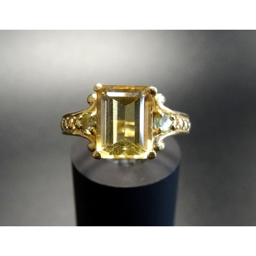 37 - YELLOW BERYL AND PERIDOT DRESS RING  the central emerald cut yellow beryl flanked by a round cut per...