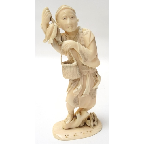 282 - CHINESE CARVED IVORY FISHERMAN standing on a tree stump with fish beside him, and holding three fish...