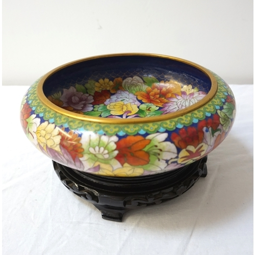 252 - CHINESE CLOISONNE CENTRE BOWL decorated with colourfull flowers on a circular hardwood stand, 23cm d...