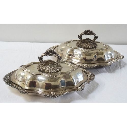 172 - PAIR OF LATE VICTORIAN SILVER PLATED SERVING DISHES of shaped outline, the lids with ornate removabl...