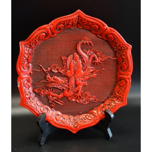 268 - CINNABAR WALL PLAQUE with a shaped border decorated with scrolls around a central dragon with a man ...