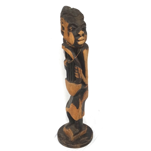 281 - CARVED WEST AFRICAN FIGURE OF A MUSICIAN or story teller, playing a Bolon, raised on a shaped base, ...