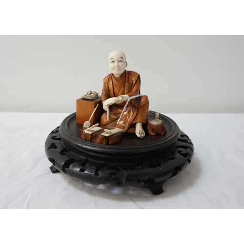 283 - CARVED JAPANESE IVORY AND BOXWOOD OKIMINO of a Noh mask maker, seated with his masks and tools aroun...